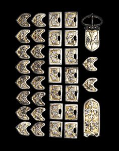 Viking Gilt Belt Suite, 9th-11th Century AD A group of silver-gilt belt mounts, a buckle and belt plate, comprising: eighteen convex shield-shaped mounts with central scrolling vine leaf and grape cluster motif, three attachment lugs to the rear;...