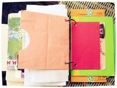 """Brights"" Junk/Smash Journal. A thick journal containing a  mix of index cards, colored paper bags, envelopes (both recycled & hand made), scraps of cardstock/decorative scrapbook papers, file folders, etc. Two book binding rings hold this journal together."