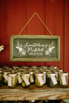 "As DIY wedding favors, Tylar and Erick gave their guests jars of Tylar's grandma's homemade spicy pickles. (We also love the presentation: the ""something pickled"" sign is too cute!)"