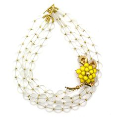 Influence of Cheer | Elva Fields | asymmetrical necklace with clear beads and a yellow flower brooch