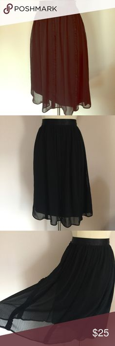 """Nicole Miller Black Ruffle Trim Flared Skirt 8 Nicole Miller black overlay skirt with Ruffle trim, and satin waistband. Skirt is fitted at the waist and flares out, with a sheer black overlay. Has cute ruffles going down the skirt, and a zippered back. Worn once for an event and dry cleaned. Looks new, with no stains or rips. Tagged a size 8 and measures 32"""" across and 29"""" from waist to hem. Had a flow fit. Nicole by Nicole Miller Skirts Midi"""