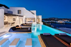 With smooth white render in classic Mykonian-Cycladic cubic design and with minimal black trim details, the stunning Villa Jalak stands out in the crowd.  Lounge in the indulgent pool with one of the best views on the island, featuring a front and centre view of yacht-lined Psarou Bay.  This home boasts five suites with king size beds, open plan living and dining areas, and a well-appointed kitchen. Take advantage of the floating daybeds by the infinity pool, or a moonlit dip in the master… Luxury Villas In Greece, Mykonos Villas, Greece Hotels, Mykonos Town, Weekly Rentals, Balcony Doors, Greece Holiday, Spa Tub, Future House