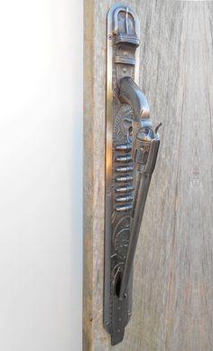 """Gun door handle. Pistol door pull mounted on cartridge belt. Cast in bronze,  antique nickel finish, 28""""."""