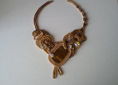 A statement bib necklace made in soutache embroidery technique with big natural stone tiger eye, natural shell beads and AAA+ class crystals. This stunning piece of jewelry is made of soutache braid, Czech beads, natural stones, crystals, and glass beads. Length of chain is adjustable.