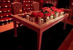 Mesa principal de estilo blanca con tapa de espejo + rosas rojas + silloncitos de estilo para los novios y fondo de estanterias con mini velas. By Mercedes Courreges Ambientaciones