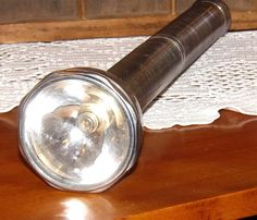Baton style silver metal extra long flash light by Ray O Vac with push button on and off switch, glass lens, belt loop and extra light bulb storage. A whopping 17 inches long and 3 inches across the lens end. All metal with ribbed body for great grip. It uses round D cell batteries which would give it some real heft. Original Ray O Vac logo. A useful display piece for the cabin or man cave.