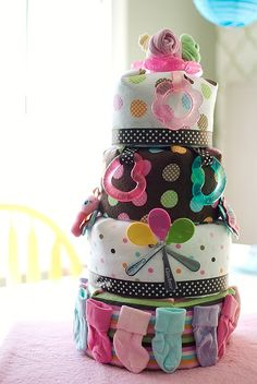 DiY- Baby Gift Cake~ This not only has diapers inside but cover it with receiving blanket and other baby items. It's a great gift and centerpiece for a shower!