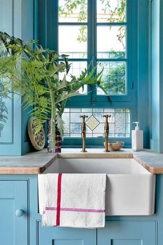 blue kitchen cabinets, farm sink & stained glass windows.