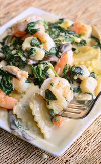 Ravioli with Seafood, Spinach & Mushrooms in Garlic Cream Sauce. Phenomenal but easy dinner to impress someone special in your life. Three cheese ravioli cooked in garlic cream sauce with shrimp, scallops, spinach and shiitake mushrooms. | from willcookforsmiles.com