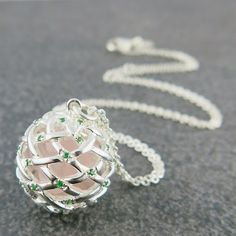 Weave Medium Ball Pendant, in Silver with Green Tsavorite gemstones on the outside, and Pink Rose Quartz rough gemstones on the inside.