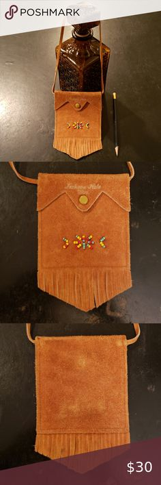 """VINTAGE JACKSON HOLE SMALL SUEDE SOUVENIR PURSE This vintage 60s small brown suede purse is darling!!! Originally a souvenir from Jackson Hole, Wyoming, it features a Native American bead design and is embossed with, """"Jackson Hole"""" on the front, snap front closure, strap and fringe on bottom. In excellent vintage condition!  Purse body measures 9""""x 4"""" and strap measures 16"""". Bags Mini Bags Jackson Hole, Native American Beading, Mini Bags, Brown Suede, Wyoming, Closure, Purses, Vintage, Best Deals"""