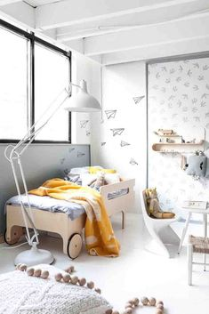 Another stunning white-based bedroom with a bed on wheels on the one end, a floor lamp and lots of grey and yellow accents. Image by Cuckooland.