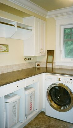 Modern white laundry room with L shape laundry cabinets