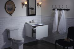 Vintage with a twist, this timeless bathroom features the neo-traditional Tresham toilet, clean white subway tile and a glass-topped compact vanity.