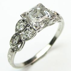 Asscher Petals: We love the combination of angular asscher cuts with sensuous, curvy mountings. Here, a bright white asscher shimmers amidst an array of diamond set diamond petals with a decidedly Art Nouveau feel.  Ca. 1910.  Maloys.com