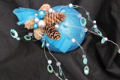 Blue ornament decorated with pine cones and miniature ornaments