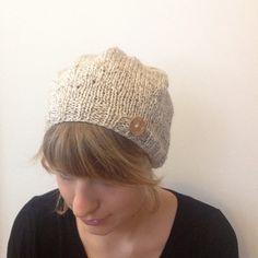 Czapka wykonana na ściągaczu w kolorze kremowym z domieszką delikatnego brązu. Do czapki doszyty jest guziczek imitujący drewno. Obwód czapki bez rozciągania: 46 cm