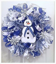 Enjoy Christmas and the Winter Season when you hang up your Blue Snowflake Snowman Deco Mesh Wreath. It is make on a wired form with high quality metallic deco mesh in royal blue, silver and white. There are elegant blue and silver snowflake ribbons with blue glittered ribbons and silky white ribbons. Flex tubing in blue and white stripe and silver glittered picks have been placed all around the wreath. You will love how the three white glittered snowflakes pop with brilliance on this wre...