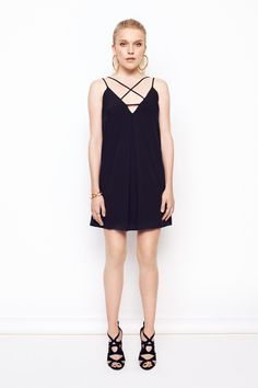 Black dress in thin polyester crepe with thin adjustable straps crossed over chest.