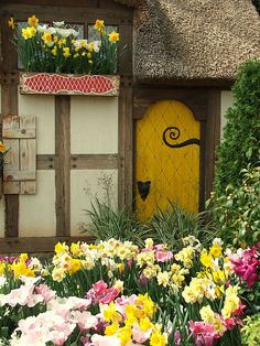 A cottage nestled in bright spring flowers in the Ginter Botanical Gardens in Richmond, Virginia
