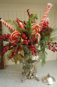 Silver chalice, tucked in with a few simple red berry picks, big peppermint candy canes and a larger-than-life sucker.