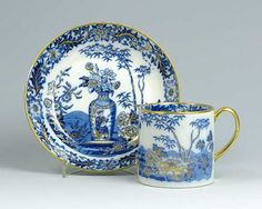 A Wedgwood pearlware can and saucer decorated in underglaze blue with a vase of flowers within a foliate border highlighted in gilt.  Impressed Wedgwood and B in gilt