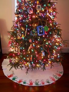 White tree skirt with children's hand prints - add new handprints each year - very cute idea!