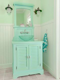 A cottage style bathroom in a seaglassy green-and-blue palette.  Wainscoting walls are outfitted with hooks for a handy spot to hang towels.