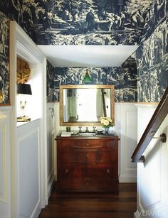 Navy Toile packs a punch in this hallway foyer! This foyer, that leads to a bathroom, unexpectedly employs navy toile wallpaper. Wallpaper, Lee Jofa; trim, Samuel & Sons. Swedish desk, Eileen Lane Antiques, as vanity. Mirror, John Rosselli.