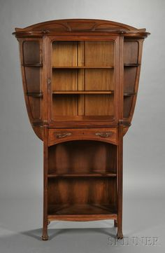 French Art Nouveau Walnut Etagere, c. 1900, with arched cresting and shaped top, the case fitted with glazed door and shelves to the interior, all flanked by graduated open shelves; with medial drawer and two open shelves; the borders with serpentine foliate designs.