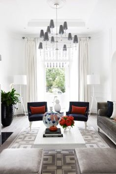 This 1940s duplex house was reconfigured from a series of apartments into one family house. A sense of grandiosity of proportion has been achieved by lowering the lounge and dining rooms and connecting them to a sunken front courtyard. A neutral palette of blacks, whites and greys get the occasional pop of blue, red and orange colours.
