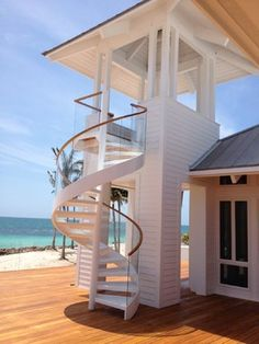 A spiral staircase is both a space saving idea and modern feature of this stunning coastal home | #coastal #home #exterior #seaside #house #contemporary