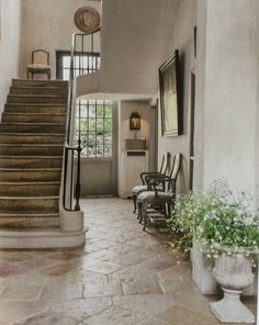 stone-like floor love! neutrals with naturals and stone urn with greenery... wall sconce.. edges are soft and rounded not squared and sharp... beautiful