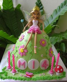 Other than the fact that I hate these Bratz-looking dolls, this is a great idea for a fun birthday cake -- a fairy perched on a mole hill (or a hobbit house?)
