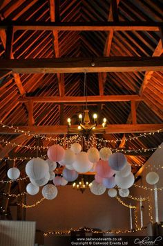 Gorgeous pale pink and lavender paper lanterns with a fairy light canopy, for a pretty barn wedding