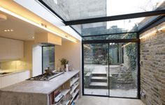 minimal windows sliding doors to side infill extension with glass roof above supported by steel T sections    www.iqglassuk.com