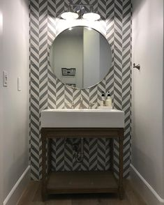 How cool does this powder bath accent wall look! The Bruges Grey pattern fits perfectly in this bathroom designed by at in Scottsdale, AZ. Reece Bathroom, Tile Accent Wall, Herringbone Tile, Concrete Tiles, Handmade Tiles, Round Mirrors, Bath Decor, Bath Design, Room Lights