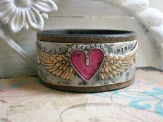 THIS LISTING IS RESERVED FOR SHELLEY.  A little cowgirl glam goes a long way on my Love Has Wings leather cuff bracelets! Each one features my signature heart bezel centered between angel wings. Hand-rubbed with an aged patina to add to their old world charm, and carefully handcrafted by me with much love in my home studio.    On this whimsical little pretty, the pink heart is a darlin shade of orchid, and is adorned with petite sparkling rhinestones. Stamped with the phrase Love Has Wings…