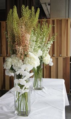 A tall, and modern arrangement, using white phalaenopsis orchids, white hydrangea, and peach eremurus. This photo was taken at the Sainte Marie Bassiere, in New Orleans, for an elegant, engagement party.