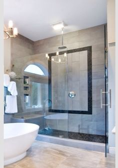 Freestanding Tub. Light colors and black. Black tile design. walk in shower. Glass.