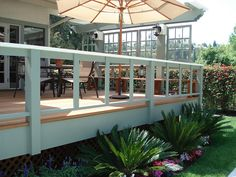 Redwood deck with light green accents, wall of floating windows and redwood bench designed by Windsor Decks & Gardens.