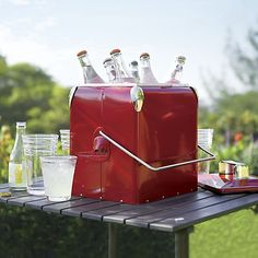 A new take on a nostalgic classic refreshes food and beverage service for day trips, picnics and entertaining. Durable steel cooler with bright red powdercoat finish is insulated and outfitted with a bottle opener and carrying handle.