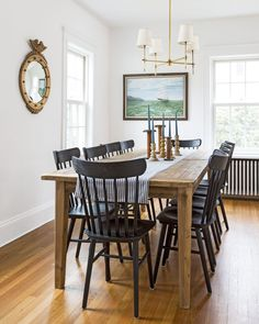 Shaker style chairs in black look striking against the wood floor and table. Very simple wall decor.