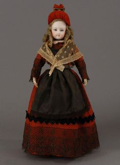 Gaultier bisque doll, ca 1870, wears original dress of red wool printed overall with a star pattern, is embellished with black lace, black silk velvet zigzag ribbon and a natural lace shawl. A classic straw hat decorated with red wool and velvet ties the presentation together nicely.