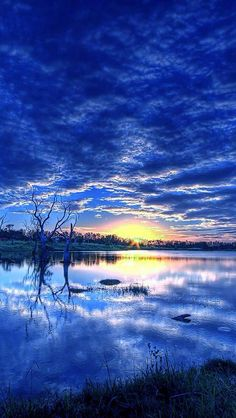 Blue sunset sky full of clouds, water