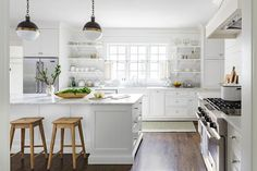 White country kitchen features white cabinets paired with white marble countertops and a shiplap backsplash.