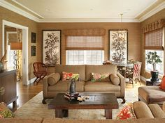 The rattan shades, coordinating beige upholstery, and natural wood furniture work together to create a cozy, warm den.