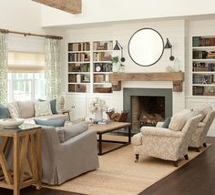 Chic cottage living room boasts gray sofas topped with blue lotus pillows and positioned on a bound jute rug facing an industrial wood top coffee table that also sits seats two side by side beige coral print roll arm accent chairs.
