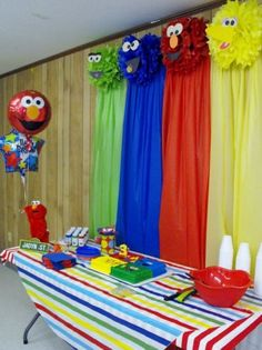 Colorful Sesame Street backdrop made from character pompoms and plastic tablecloths.  See more Elmo birthday party ideas at www.one-stop-party-ideas.com