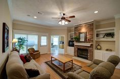 Anchored by a floor to ceiling brick fireplace flanked by built-ins for additional storage, the spacious living room features a wall of windows overlooking the backyard for natural light and backyard views.
